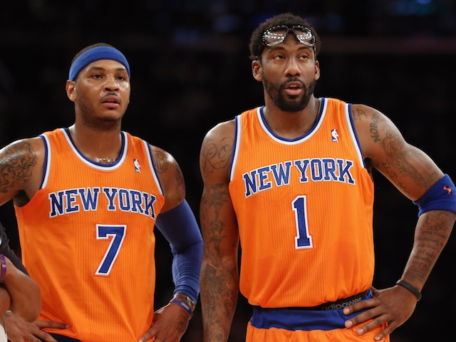 Carmelo Anthony and Amar'e Stoudemire of the New York Knicks watch on against the Boston Celtics at Madison Square Garden on December 8, 2013