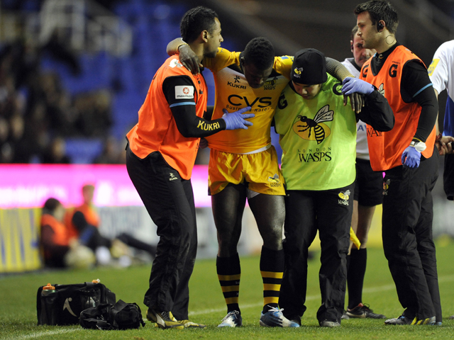 Christian Wade of London Wasps leaves the pitch after a suspected injury to his ankle during the Aviva Premiership Rugby match between London Irish and London Wasps at the Madejski Stadium on November 30, 2013