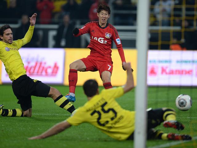 Leverkusen's South Korean striker Heung Min Son scores past Dortmund's defender Manuel Friedrich and Dortmund's Greek defender Sokratis during the German first division Bundesliga football match Borussia Dortmund vs Bayer Leverkusen in the western German