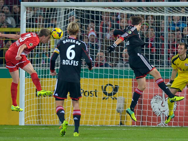 Freiburg's Matthias Ginter heads in his team's opening goal against Bayer Leverkusen during the 3rd round of the German Cup on December 4, 2013