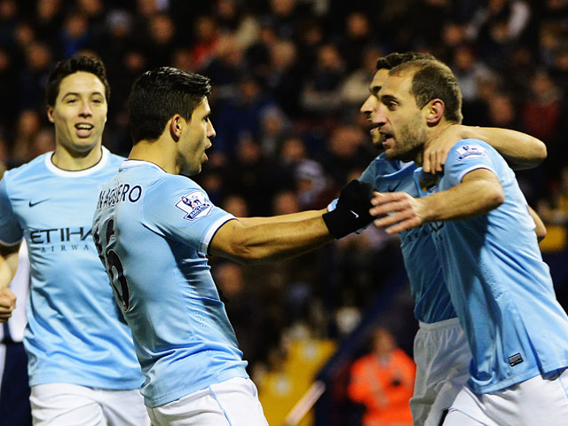 Man City's Sergio Aguero celebrates with teammates after scoring his team's opening goal against West Brom during their Premier League match on December 4, 2013