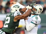 Marcus Dowtin #92 of the New York Jets is called for roughing the passer as he collides with Matt Moore #8 of the Miami Dolphins on October 28, 2012