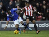 Genseric Kusunga of Oldham Athletic is tackled by Kadeem Harris of Brentford during the Sky Bet League One match between Brentford and Oldham Athletic at Griffin Park on December 14, 2013