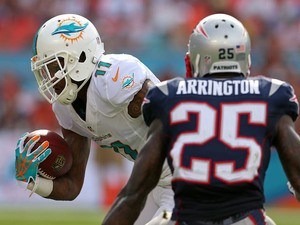 Mike Wallace #11 of the Miami Dolphins makes a catch in front of Kyle Arrington #25 of the New England Patriots during a game at Sun Life Stadium on December 15, 2013