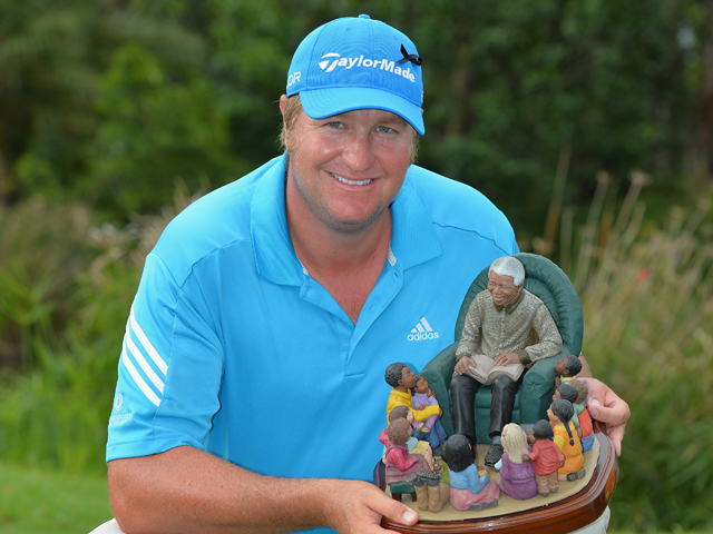 Dawie Van Der Walt of South Africa holds the trophy after winning the Nelson Mandela Championship at Mount Edgecombe Country Club on December 14, 2013