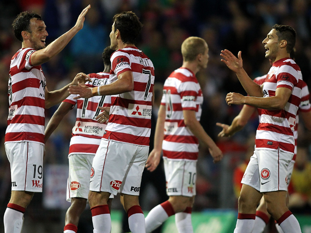 Mark Bridge of the Wanderers celebrates with team mates after scoring a goal during the round 10 A-League match between the Newcastle Jets and the Western Sydney Wanderers at Hunter Stadium on December 14, 2013