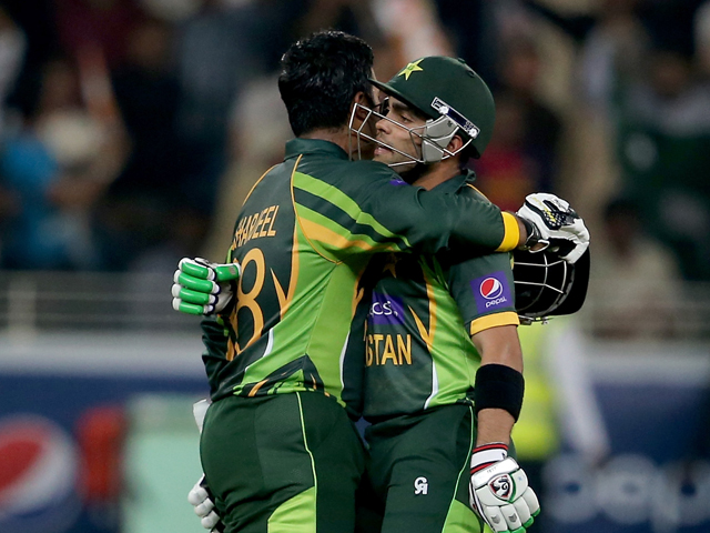 Umar Akmal congratulate Sharjeel Khan during the second Twenty20 International match between Pakistan and Sri Lanka at Dubai Sports City Cricket Stadium on December 13, 2013