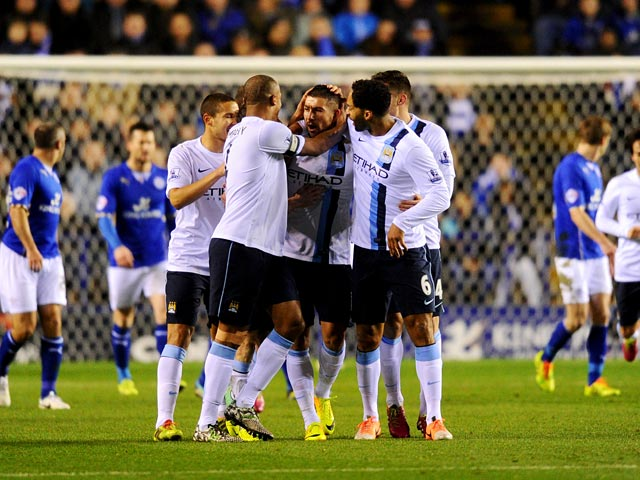Man City's Aleksandar Kolarov is congratulated by teammates after scoring the opening goal against Leicester during their Capital One Cup quarter-final match on December 17, 2013