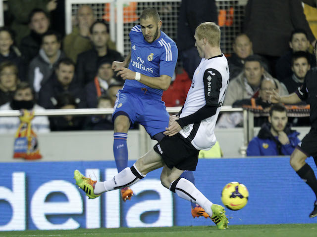Real Madrid's French forward Karim Benzema vies for the ball with Valencia's French defender Jeremy Mathieu during the Spanish league football match on December 22, 2013