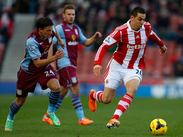Aleksander Tonev of Aston Villa competes for the ball with Geoff Cameron of Stoke during the Barclays Premier League match between Stoke City and Aston Villa at the Britannia Stadium on December 21, 2013