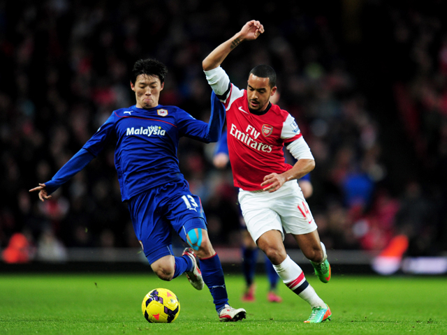 Theo Walcott of Arsenal takes on Kim Bo-Kyung of Cardiff City during the Barclays Premier League match between Arsenal and Cardiff City at Emirates Stadium on January 1, 2014