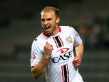 MK Dons' Luke Chadwick celebrates after scoring the opening goal against Wigan during their FA Cup third round replay match on January 14, 2014