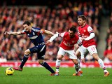 Sascha Riether of Fulham evades Santi Cazorla and Nacho Monreal of Arsenal during the Barclays Premier League match on January 18, 2014