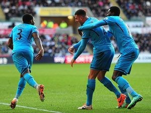 Tottenham's Kyle Walker celebrates his team's second goal with teammates Danny Rose and Emmanuel Adebayor against Swansea during their Premier League match on January 19, 2014