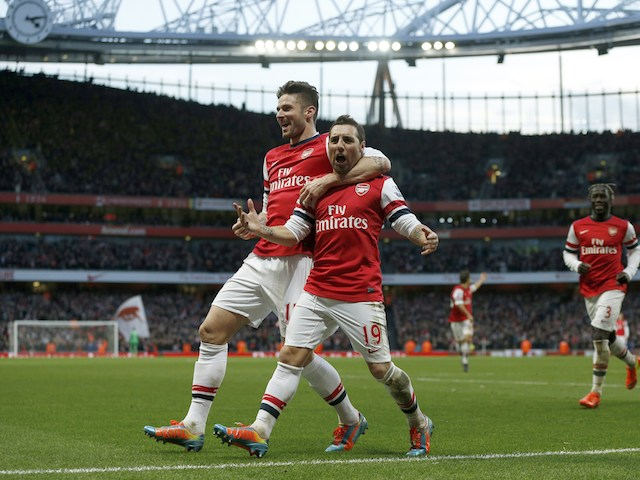 Arsenal's Spanish midfielder Santi Cazorla celebrates scoring the opening goal with teammate Olivier Giroud during the English Premier League football match against Fulham on January 18, 2014