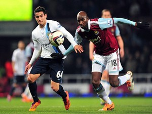 Manchester City's Portuguese midfielder Marcos Lopes (L) vies with West Ham United's French midfielder Alou Diarra (R) during the English League Cup semi-final second leg football match on January 21, 2014