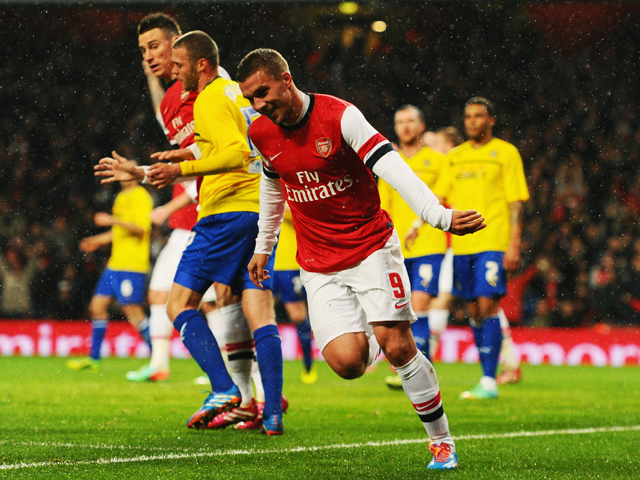 Lukas Podolski of Arsenal celebrates as he scores their second goal with a header during the FA Cup with Budweiser Fourth round match between Arsenal and Coventry City at Emirates Stadium on January 24, 2014