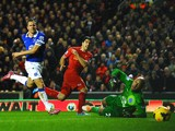 Luis Suarez of Liverpool scores his team's fourth goal past goalkeeper Tim Howard of Everton as Phil Jagielka of Everton closes in during the Barclays Premier League match between Liverpool and Everton at Anfield on January 28, 2014