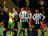 Referee Chris Foy shows Loic Remy of Newcastle United a red card during the Barclays Premier League match between Norwich City and Newcastle United at Carrow Road on January 28, 2014