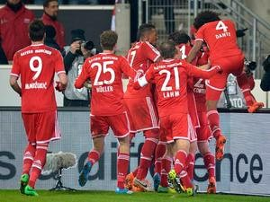 Bayern Munich's Thiago is mobbed by teammates after scoring his team's second goal against Stuttgart during their Bundesliga match on January 29, 2014
