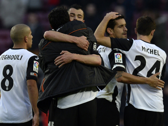 Valencia's football players celebrate their victory at the end of the Spanish league football match FC Barcelona vs Valencia CF at the Camp Nou stadium in Barcelona on February 1, 2014
