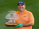 Kevin Stadler poses with the championship trophy after winning the Waste Management Phoenix Open at TPC Scottsdale on February 2, 2014