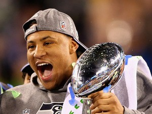 Outside linebacker and Super Bowl MVP Malcolm Smith #53 of the Seattle Seahawks holds the Vince Lombardi Trophy after winning Super Bowl XLVIII on February 2, 2014