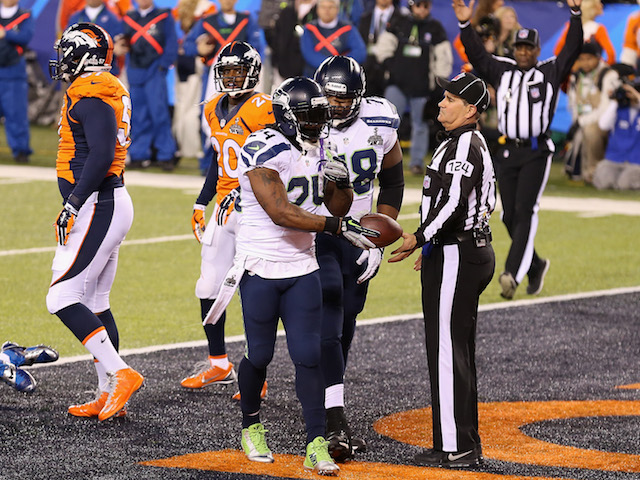 Running back Marshawn Lynch #24 of the Seattle Seahawks hands ball over after scoring a one yard touchdown against the Denver Broncos on February 2, 2014