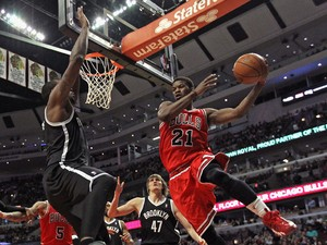 Jimmy Butler #21 of the Chicago Bulls leaps to pass around Andray Blatche #0 of the Brooklyn Nets at the United Center on February 13, 2014