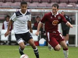 Jake Nicholson of Tottenham Hotspur looks to play the ball watched by Steve Guinan of Northampton Town during a Behind Closed Doors Friendly Match between Northampton Town and Tottenham Hotspur at Sixfields Stadium on October 19, 2010