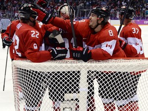 Canada's players celebrating after winning the Men's Ice Hockey Semifinal match between the USA and Canada at the Bolshoy Ice Dome during the Sochi Winter Olympics on February 21, 2014