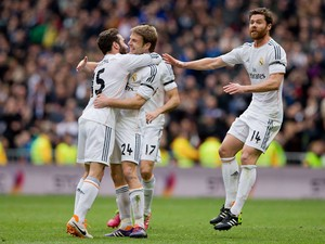 Asier Illarramendi of Real Madrid CF celebrates scoring their opening goal with teammates Daniel Carvajal and Xabi Alonso (R) during the La Liga match between Real Madrid CF and Elche CF at Estadio Santiago Bernabeu on February 22, 2014