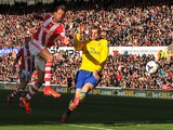 Stoke City's English forward Peter Crouch shoots wide as Arsenal's German defender Per Mertesacker tries to defend during the English Premier League football match between Stoke City and Arsenal at the Britannia Stadium in Stoke-on-Trent on March 1, 2014