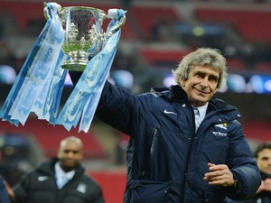 Manuel Pellegrini, manager of Manchester City celebrates victory with the trophy after the Capital One Cup Final against Sunderland on March 2, 2014
