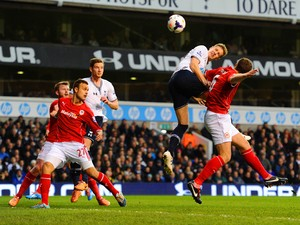 Michael Dawson of Tottenham Hotspur heads towards goal under pressure from Ben Turner of Cardiff City during the Barclays Premier League match between Tottenham Hotspur and Cardiff City at White Hart Lane on March 2, 2014