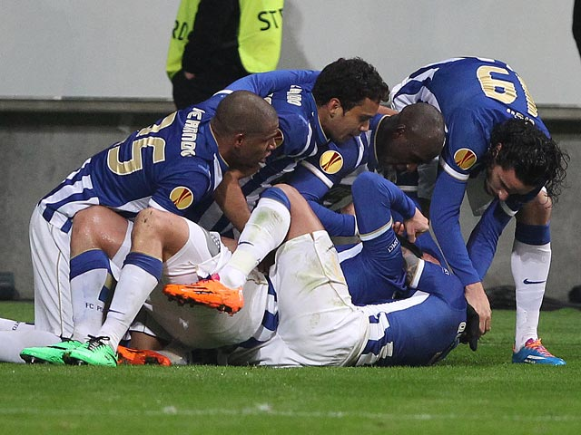 Porto's Nabil Ghilas is mobbed by teammates after scoring his team's third goal against Eintracht Frankfurt during their Europa League match on February 27, 2014