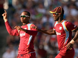 West Indies cricketer Marlon Samuels and team captain Darren Sammy celebrate dismissing England's batsman Eoin Morgan during the first T20 match between England and West Indies at the Kensington Oval in Bridgetown on March 9, 2014