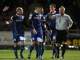 Matthew Lund of Rochdale is shown a red card by referee Mark Heywood after receiving a second yellow card for his celebration after scoring against Northampton on March 18, 2014