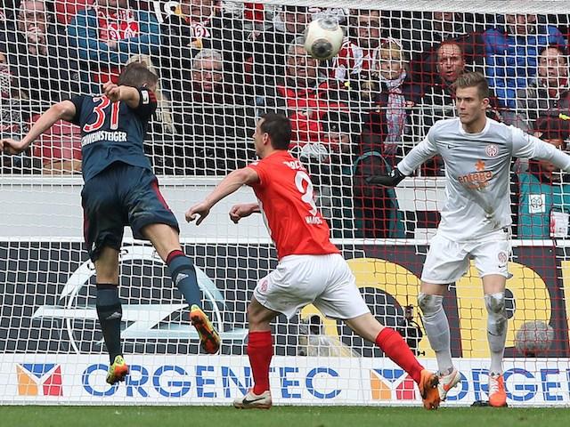 Bayern Munich's midfielder Bastian Schweinsteiger (L) heads the ball to score 0-1 during the German first division Bundesliga football match against FSV Mainz 05 on March 22, 2014