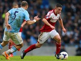 Patrick Roberts of Fulham is tracked by Pablo Zabaleta of Manchester City during the Barclays Premier League match between Manchester City and Fulham at Etihad Stadium on March 22, 2014