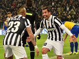 Juventus' Argentinian foward Carlos Tevez celebrates after scoring a second goal with teammate Juventus' Chilean midfielder Arturo Vidal during the Italian Serie A football match Juventus vs Parma at 'Juventus Stadium' in Turin on March 26, 2014