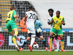 Jonathan de Guzman of Swansea City scores the opening goal during the Barclays Premier League match against Norwich City on March 29, 2014