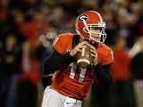 Quarterback Aaron Murray #11 of the Georgia Bulldogs rolls out and looks downfield during the game against the Kentucky Wildcats at Sanford Stadium on November 23, 2013