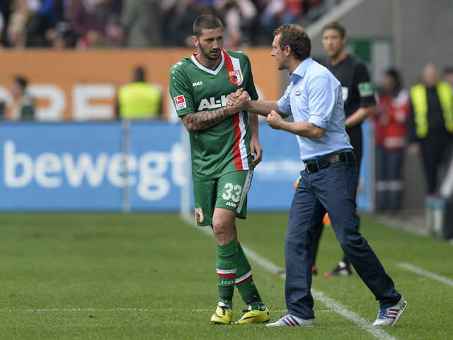 Augsburg's head coach Markus Weinzierl and Augsburg's striker Sascha Moelders shake hands after scoring during the German first division Bundesliga football match FC Augsburg vs FC Bayern Munich on April 5, 2014