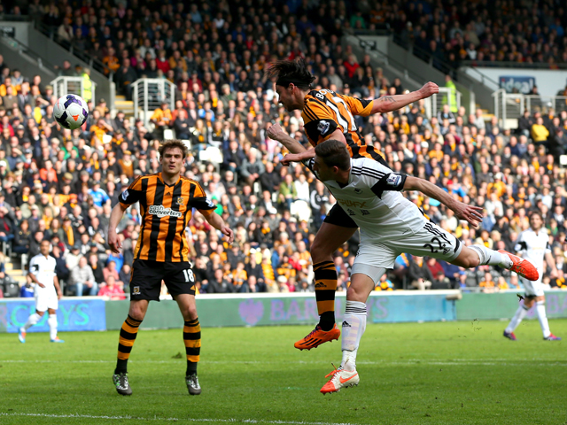 George Boyd of Hull City rises above Angel Rangel of Swansea to score the opening goal with a header during the Barclays Premier league match between Hull City and Swansea City at KC Stadium on April 5, 2014