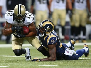 Marques Colston #12 of the New Orleans Saints is tackled after making a catch against Darian Stewart #20 of the St. Louis Rams at the Edward Jones Dome on December 15, 2013