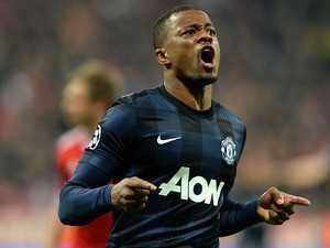 Manchester United's Patrice Evra celebrates after scoring the opening goal against Bayern Munich in the Champions League quarter final match on April 9, 2014