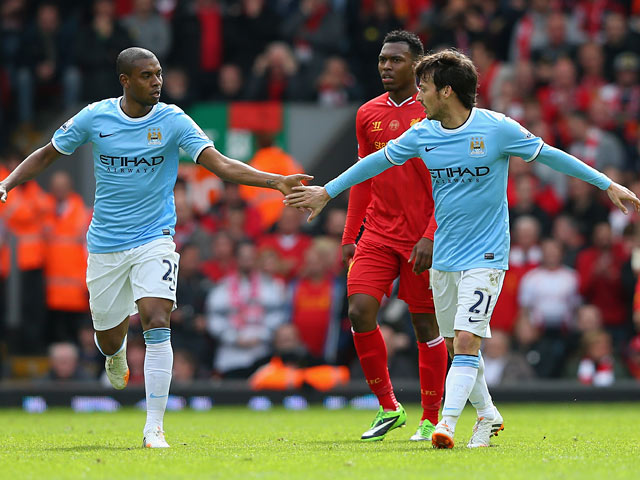 Manchester City's David Silva celebrates with team mate Fernandinho after scoring his team's first goal against Liverpool during the Premier League match on April 13, 2014