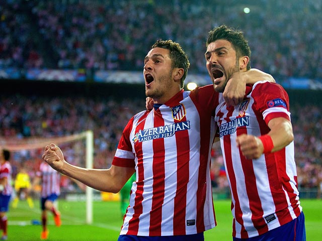 Atletico Madrid's Koke celebrates with team mate David Villa after scoring the opening goal against Barcelona during their Champions League quarter final match on April 9, 2014