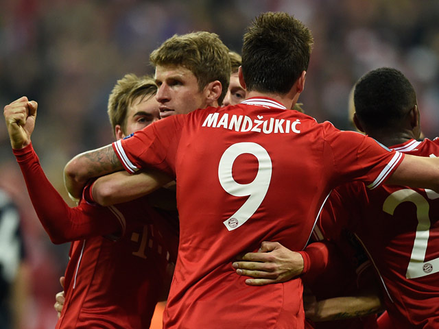 Bayern Munich's Thomas Muller celebrates with teammates after scoring his team's second goal against Manchester United in the Champions League quarter final match on April 9, 2014